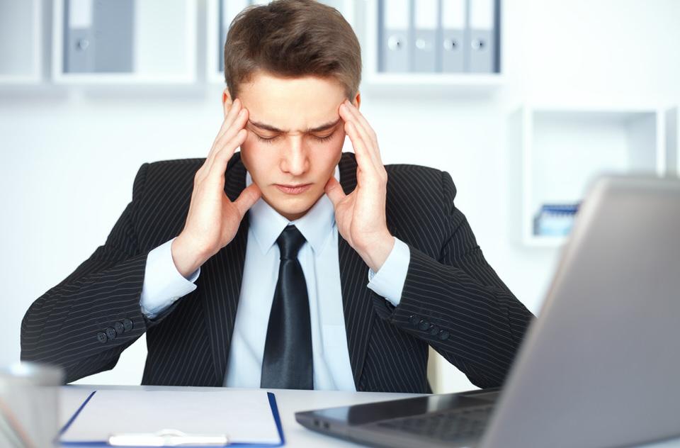 pain-relief-praxis-ganzeheitliche-schmerztherapie-mann-kopfweh-anzug-business-buero