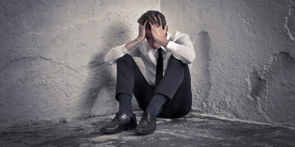 pain-relief-praxis-ganzheitliche-schmerztherapie-mann-psychische-probleme-kopfweh-sitzt-ecke-boden
